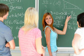 Students standing front of chalkboard — Stock Photo