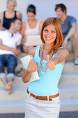 Student girl giving thumb-up — Stock Photo