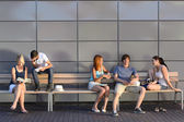 College students sitting on bench — Stock Photo