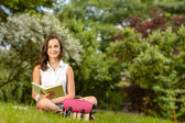 Girl sitting on grass with book — Stock Photo