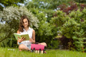 Girl reading book on grass — Stock Photo