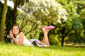 Girl lying on grass listen music — Stock Photo