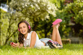 Girl with headphones lying on grass — Stockfoto