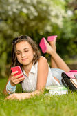 Girl with phone on grass — Stock Photo