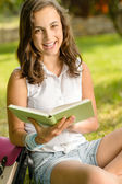 Girl sitting grass read book — Foto de Stock