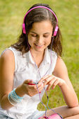 Girl with headphones sitting on grass — 图库照片