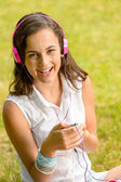 Girl listen music sitting on grass — Stock Photo