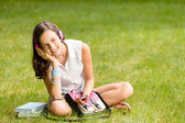Girl with headphones sitting on grass — Photo