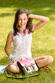 Student girl sitting on grass — Stock Photo