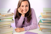 Girl between stacks of books — Stock Photo