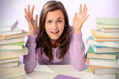 Student girl between stacks of books — Stock Photo