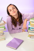 Girl between stacks of books — Stockfoto