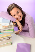 Girl resting head on books — Stok fotoğraf