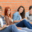 Group of friends students sitting in row — Stock Photo