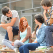 Group of friends sitting bench outside college — Stock Photo #49566743