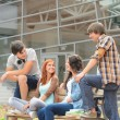Students friends sitting bench front of university — Stock Photo #49566789