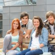 Students friends sitting bench outside campus — Stock Photo #49566815
