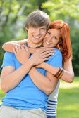 Young loving couple hugging in sunny park — Stock Photo