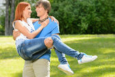 Teenage boyfriend carry girlfriend in his arms — Stock Photo