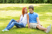 Teenage couple sitting grass looking each other — Stock Photo