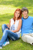 Teenage couple sitting on grass embracing summer — Stock Photo