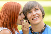Teenage woman whispering to her boyfriend outdoors — Stock Photo