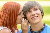 Dospívající žena šeptem svého přítele venku — Stock fotografie