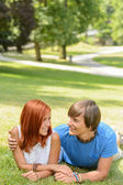 Teenage couple lying in sunny park — Stock Photo