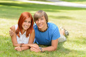 Teenage couple lying on grass summer love — Stock Photo