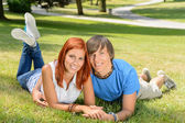 Smiling couple lying in park first love — Stockfoto