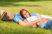 Teenage couple enjoying sun lying on grass — Stock Photo