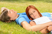 Teenage couple relaxing on grass closed eyes — Stock Photo
