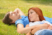 Romantic teenage couple lying on grass summer — Stock Photo