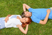 Teenage couple lying on grass — Stock Photo