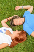 Romantic love young couple lying on grass — Stock Photo