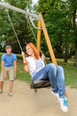 Playful teenage couple girl on swing — Stock Photo