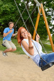 Laughing teenage couple on swing in park — Stock Photo