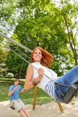 Two teenagers on swing playground in park — Stock Photo