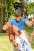 Boyfriend and girlfriend enjoying date on swing — Stock Photo