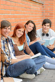 College students sitting outside by brick wall — Foto Stock