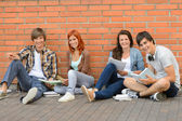 College students sitting ground by brick wall — Stok fotoğraf