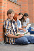 Studying boy friends sitting ground outside campus — Stock Photo