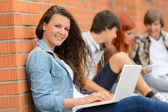 Student girl outside campus with laptop friends  — Stock Photo