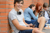 College student boy sitting ground with friends — Stok fotoğraf