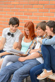 Group of students sitting bench outside college — Stock Photo
