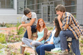 Student friends sitting outside campus laughing — Stock Photo