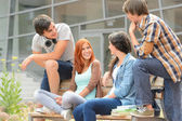 Group of friends sitting bench outside college — Stok fotoğraf