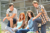 Group of students sitting bench front college — Foto Stock