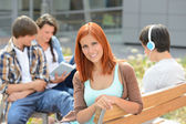 Student girl sitting outside campus with friends — Photo