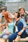 Cheerful friends hanging out by college campus — Stockfoto